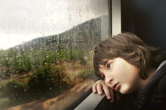 leegte- futloos jongen bij raam -groot