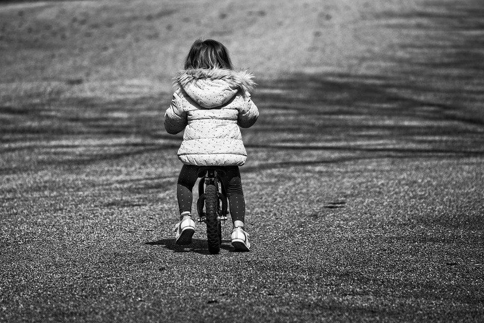 balans meisje op fiets zwart wit